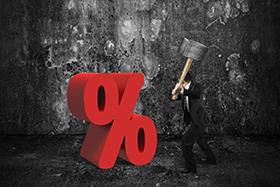 Businessman holding sledgehammer hitting red percentage sign with dark concrete room background